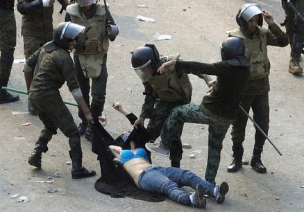 Egyptian army soldiers beat a female protester during clashes at Tahrir Square in Cairo